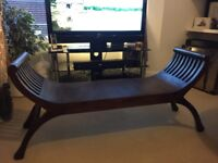 Curved wooden seat from Villa and Hut