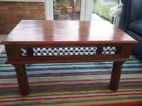 Coffee table with chunky legs and fretwork around base of table top