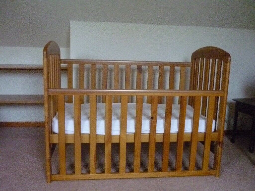 Beechwood cot with a drop side.
