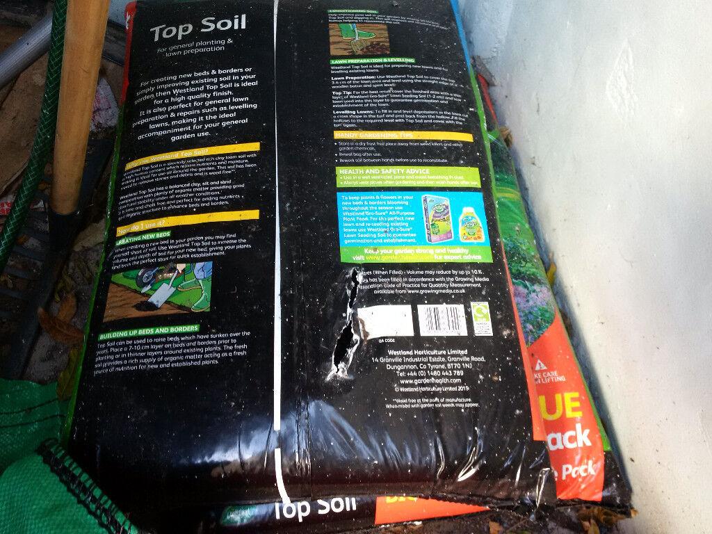 2 bags of topsoil, red watering can, rake