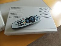 white sky box with remote control and power cable