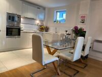 2 White leather dining chairs with chrome legs.