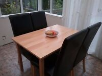 Dining table & four chairs. Pine table, black faux leather chairs. Suitable for refurbishment.