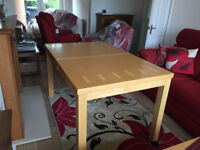 Extendable beech veneer dining room table and four matching chairs.