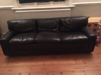 Long black leather sofa, some ware and tear but generally in good repair