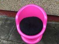 Pink plastic chair with storage room inside