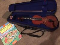Childs half size violin with case, resin, and book in good condition