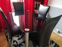 Black glass dining table with 4 chairs.