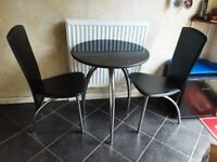 Small dining table and two chairs.