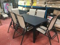 LARGE BLACK PLASTIC TABLE AND 6 CHAIRS..