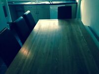 Large oak dinning table and six brown leather chairs