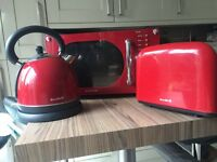 Red kitchen appliance set microwave, toaster and kettle