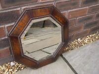 A small oak framed octagonal mirror with bevelled edges.