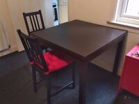 Brown extendable dining table (IKEA Bjursta) along with chairs (IKEA Stefan) with cushions