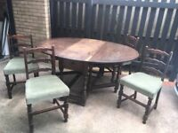 Approx. 80 year old, well loved oak table with drop sides and small drawer, includes four chairs
