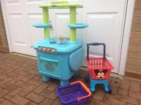 Child's toy kitchen, shopping trolley and basket