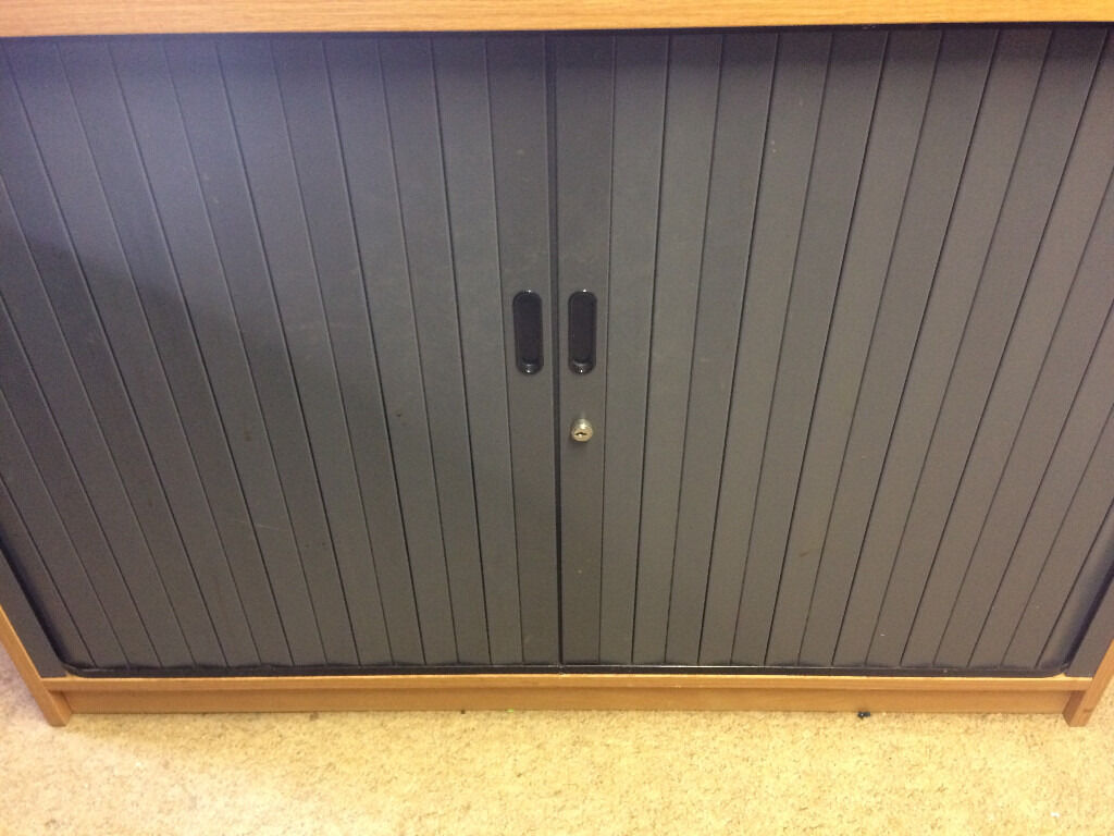 Office Cabinet with roller door, light oak, lockablein Fareham, HampshireGumtree - Office Cabinet, light oak, with roller shutter doors, a few minor scratches, adjustable shelf and clips, lockable Size Deep (front to back) 600 mm, Length 1070 mm, height 730 mm. Would look nice in a home office, or normal office environment, or use...