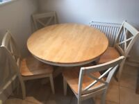 Wooden, round dining with four dining chairs.