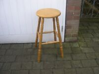 A tall pine kitchen stool with round seat.
