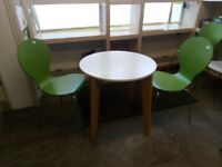 Dining room table. Round in white with 2 green chairs