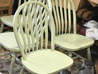 Three light green spray painted kitchen chairs