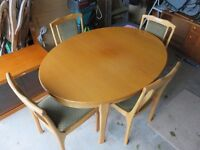 "Dining Table and four matching Dining Chairs. Oval table, in teak, size 53"" x 39"", extends to 71""."