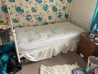 Single cream metal frame bed.