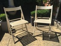 Two retro cream folding chairs.