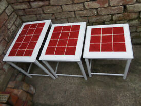 Nest of tables in white with red tile inlay