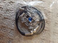 Celtic Cross style pendant with cord. Blue jewel in the centre. In excellent condition