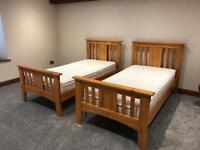 Two single bedsteads c/w mattress (solid slats)
