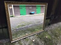 Large over mantle mirror with antique looking frame.