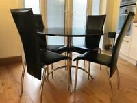 Black granite-top dining table with 4 leather dining chairs