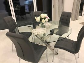 Glass dining table with chrome legs and 6 grey and chrome chairs. NEW. (Used in show house only)