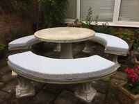 Circular stone garden table and 3 bench seats with cushions