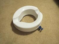 Raised toilet seat in white washable plastic