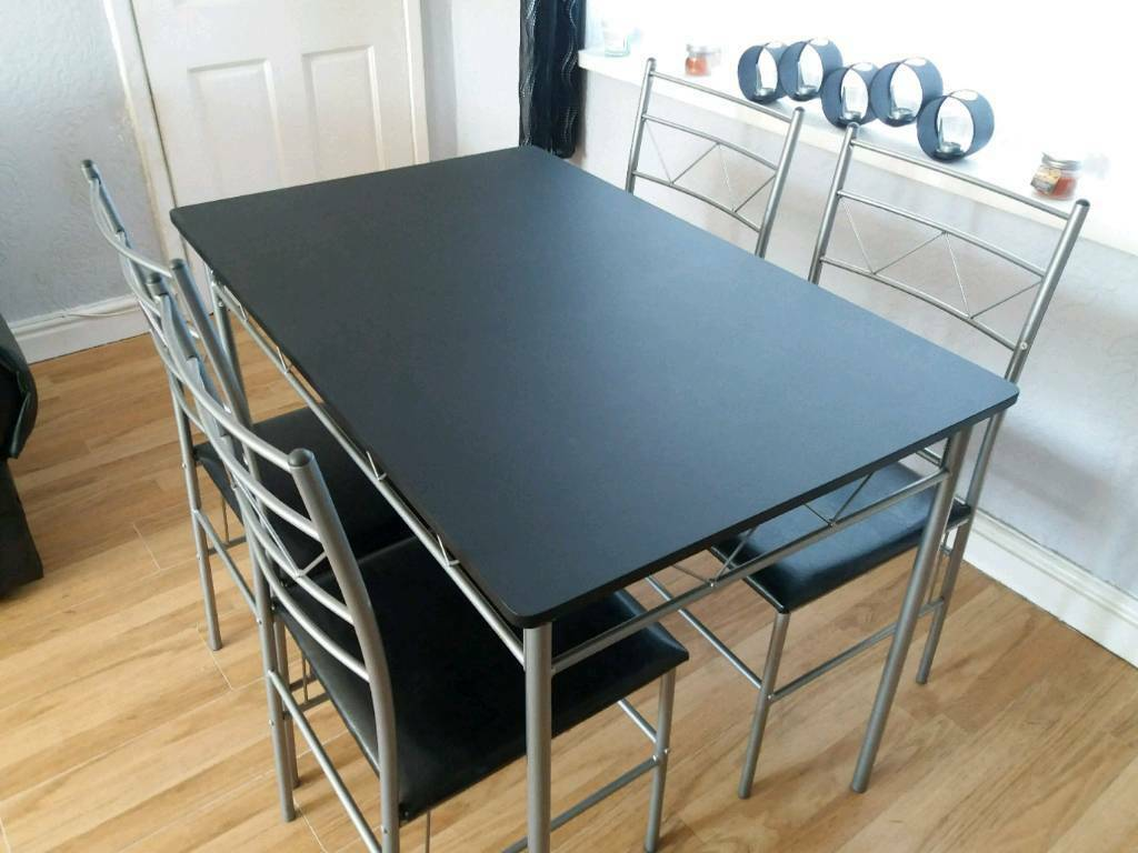 Black dinning table and four chairs in good condition sell because ...