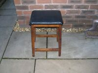 A kitchen stool with black leatherette seat.