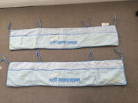 2 blue cot bumpers with train design.