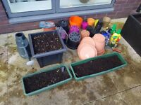 Various gardening items, pots, some with soil, rose/plant feed, watering can