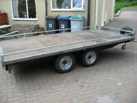 FLAT BED FOUR WHEELED TRAILER.