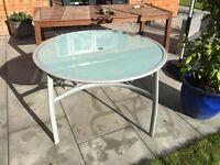 Garden table, glass top, metal legs, measuring 122cm in diameter.