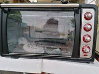 New Unused Howell Multi Pizza Oven, 1 full tray, 3 Pizza trays,plus Rottisary