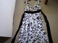 Black and white dress with ties to the back, side hidden zip. Size 14