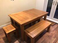 Solid oak extending dining table with matching benches and stools