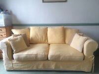 A super comfy beige sofa bed with lots of pillows