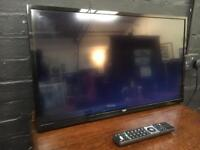 Nice clean Bush flat screen wall hanging TV complete with remote