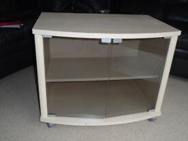 TV cabinet in light wood effect colour with glass doors and shelf and on castors