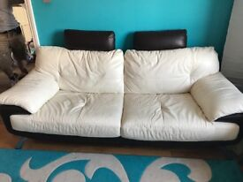 Two cream and brown leather sofas.