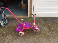Toddlers push tricycle